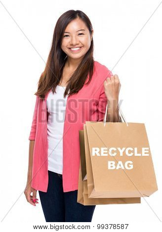 Happy woman with shopping bag and showing recycle bag