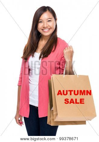 Happy woman with shopping bag and showing autumn sal
