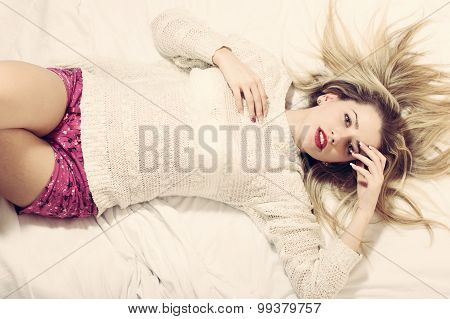 beautiful blond young woman on bed happy smiling