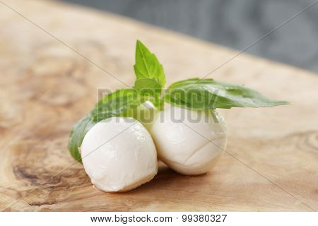 small balls of mozzarella with basil leaves