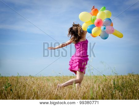 young woman holding air balloons on summer blue sky