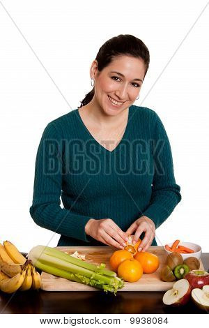 Woman In Kitchen Peeling Orange