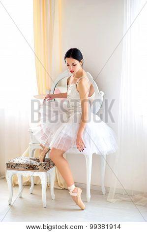 Beauty brunette ballerina in interior, wearing ballet skirt and corset