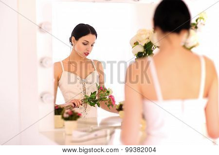 Beautiful young ballerina standing against mirror and looking at her flowers