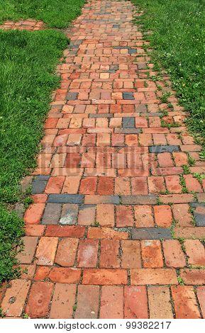 Pretty brick walkway on grassy lawn