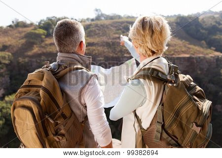 rear view middle aged of hikers pointing at distance