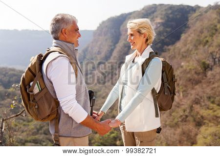 loving middle aged couple holding hands in mountain