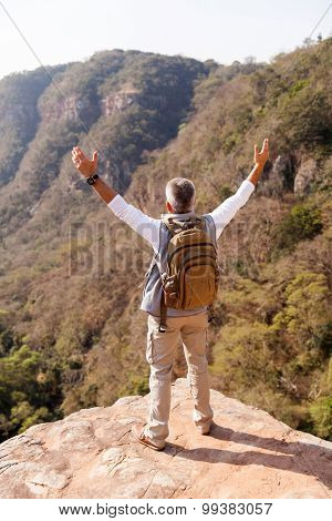 senior male hiker with arms open on top of the mountain