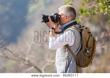 mid age hiker taking photos in mountain valley