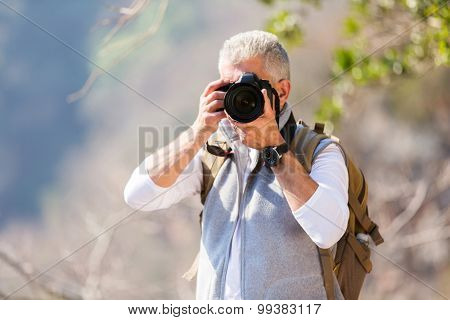 middle aged man taking photos in mountain valley with dslr camera
