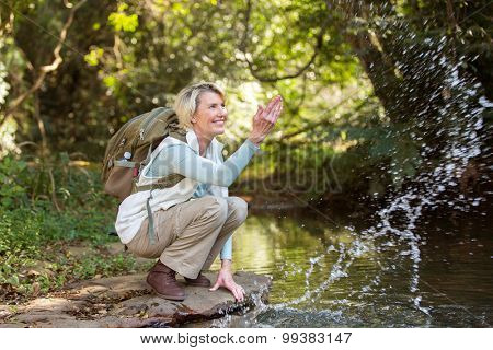 cheerful middle aged female hiker playing with stream water