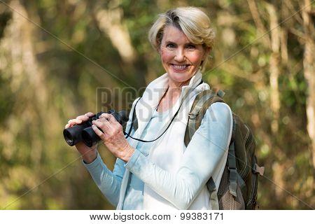 portrait of beautiful female hiker with binoculars