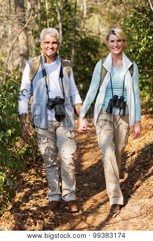cheerful middle aged couple hiking outdoors in the mountain