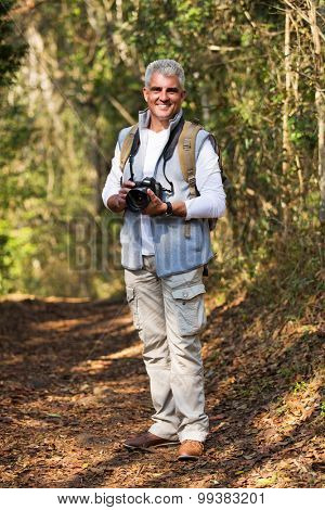 cheerful mid age man with dslr camera standing in forest