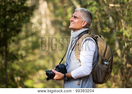 handsome man hiking in mountain with dslr camera