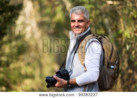 good looking mid age man taking photos in the nature