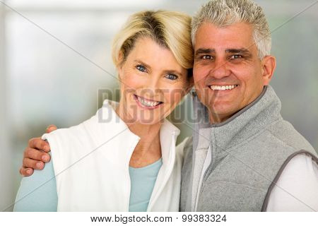 happy mid age couple standing at home