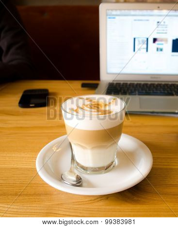 Glass coffee mug on wooden table with laptop