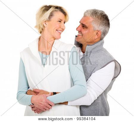 cheerful senior couple looking at each other on white background