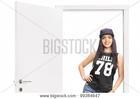 Young woman in hip hop clothes posing by an open door isolated on white background