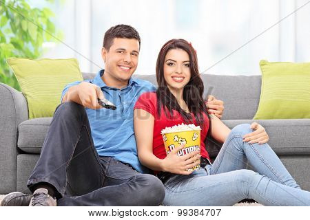 Young couple watching TV seated on the floor at home