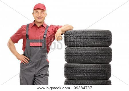 Handsome young male mechanic leaning on a stack of tires isolated on white background