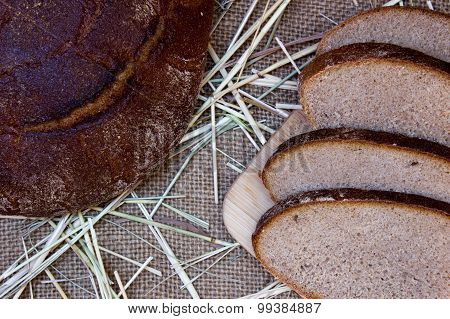 Black Bread On Burlap Background.