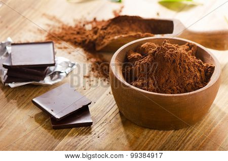 Chocolate Bars With Wooden Bowl Of Cacao Powder.