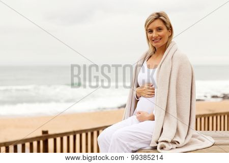 happy pregnant woman wrapped in blanket outdoors