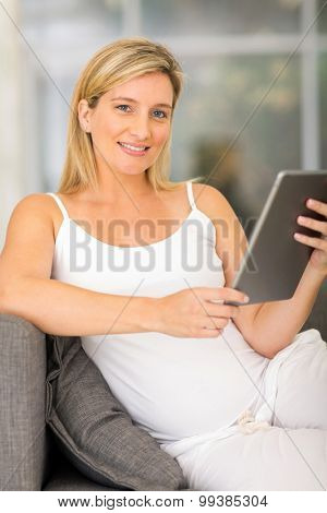 beautiful pregnant woman with tablet computer at home