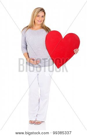 happy young pregnant woman holding red heart symbol