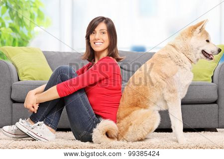 Young woman posing seated back to back with her pet dog in front of a modern gray sofa at home
