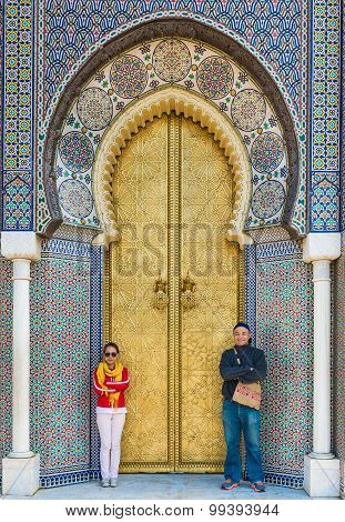 Two Asian Tourist Stand In Front Of Bab Dar Lmakhzen Or The Royal Palace Gate