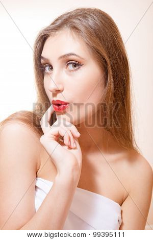 Closeup picture of astonished young female with her finger on her lips