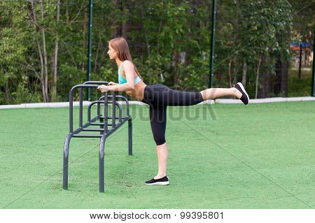 Girl In Sportswear On The Playground Doing Fitness.