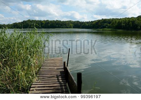Old Wooden Pier And Cane On Lake.