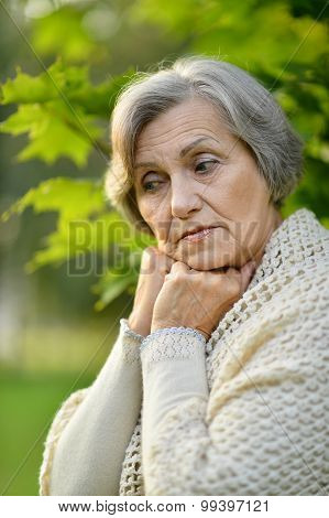 Sad eldery woman in park