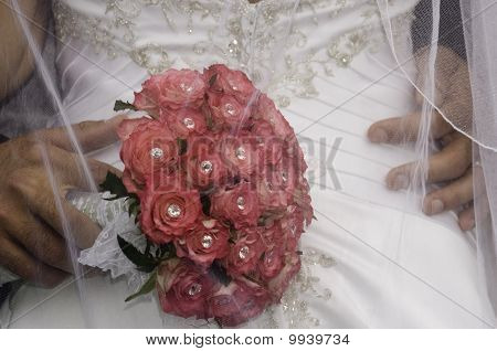 groom standing with his hand red bouquet on brides bum