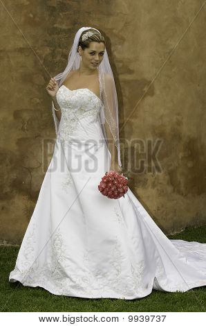 just married bride standing with bouquet against a brown wall