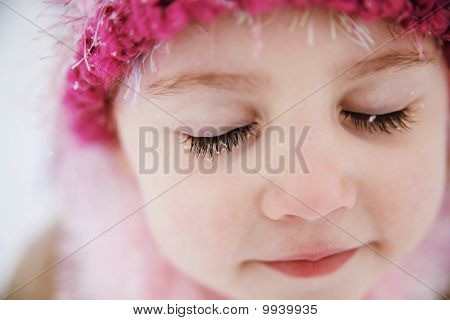 Girl with snowflakes on eyelashes