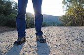 foto of dirt road  - A man standing on a gravel road with his shadow in front of him - JPG