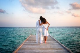 stock photo of jetties  - Sensual love couple with white clothes holding each other on a jetty on Maldives - JPG