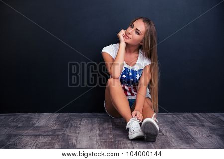Portrait of a thoughtful young girl sitting on the floor on gray background and looking away