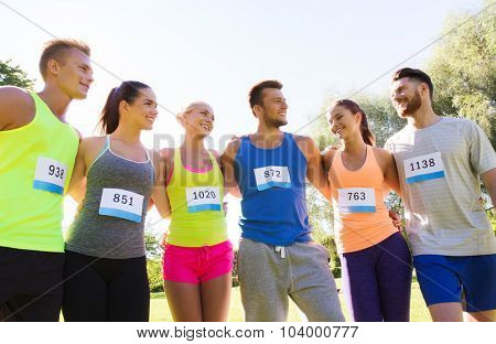 fitness, sport, marathon, friendship and healthy lifestyle concept - group of happy teenage friends or sportsmen couple with racing badge numbers outdoors