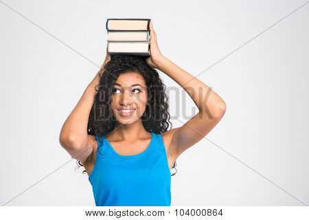 Portrait of a happy afro american woman holding books on the head isolated on a white background