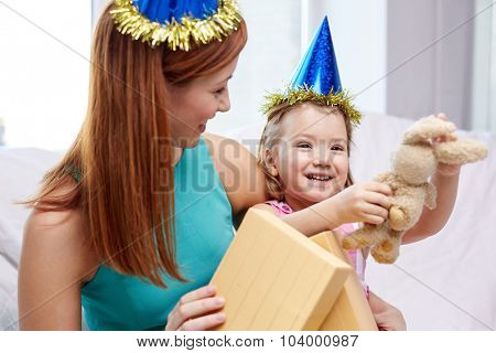 holidays, birthday, family, childhood and people concept - happy mother and little girl in party caps with gift box and toy at home
