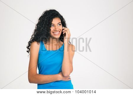 Portrait of a smiling afro american woman talking on the phone and looking away isolated on a white background