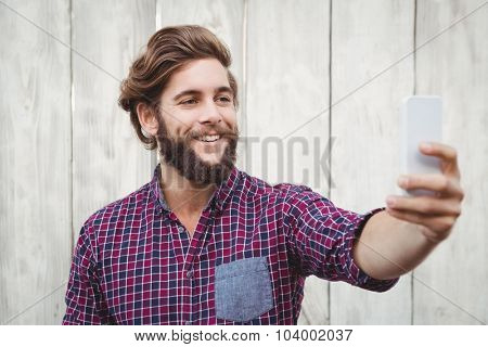 Happy hipster taking selfie against wooden wall