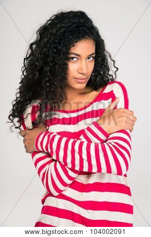 Portrait of a beautiful afro american woman posing with arms folded isolated on a white background