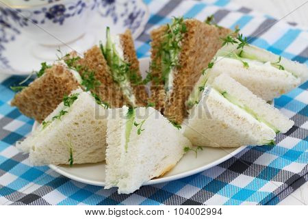 White and brown cream cheese and cucumber sandwiches on checkered cloth